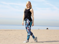 Stylish woman on beach modeling activewear