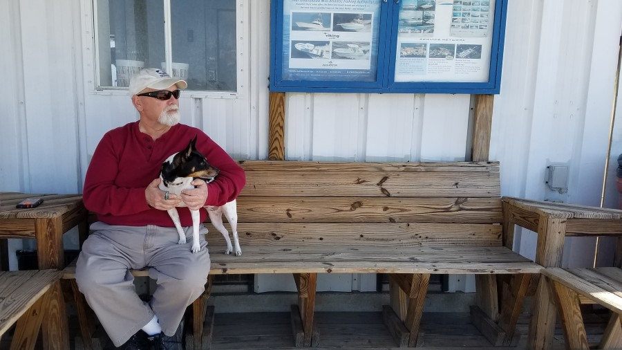 Fish Cleaner Bucky Mann sits with his dog Maggie