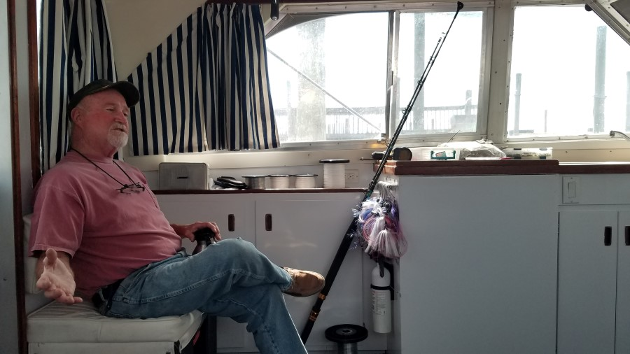 Captain Frank Smith sitting and talking aboard his boat