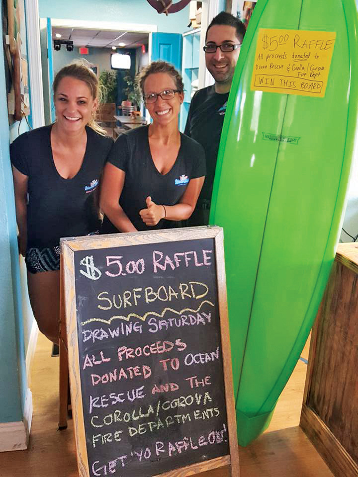 Uncle Ike's employees with surfboard up for raffle