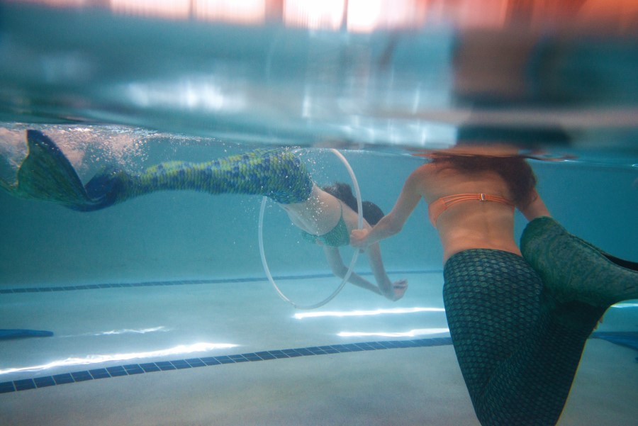 A mermaid swims through a hula hoop for practice