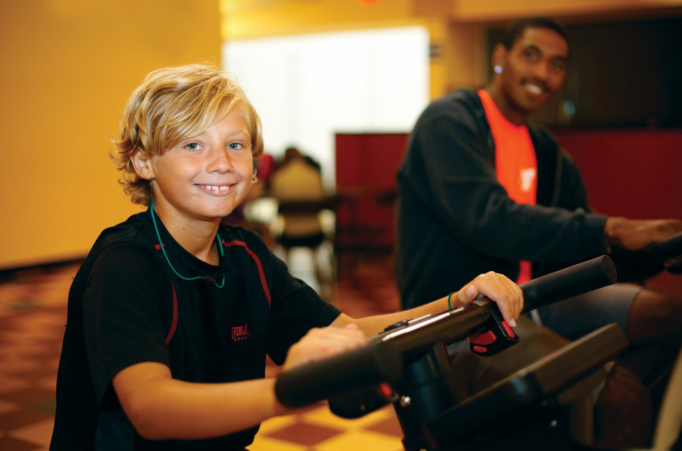 Child and young adult on workout equipment at the Outer Banks Family YMCA