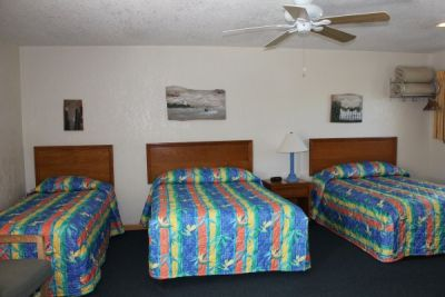 Room with two double beds and a twin bed at Pony Island Motel